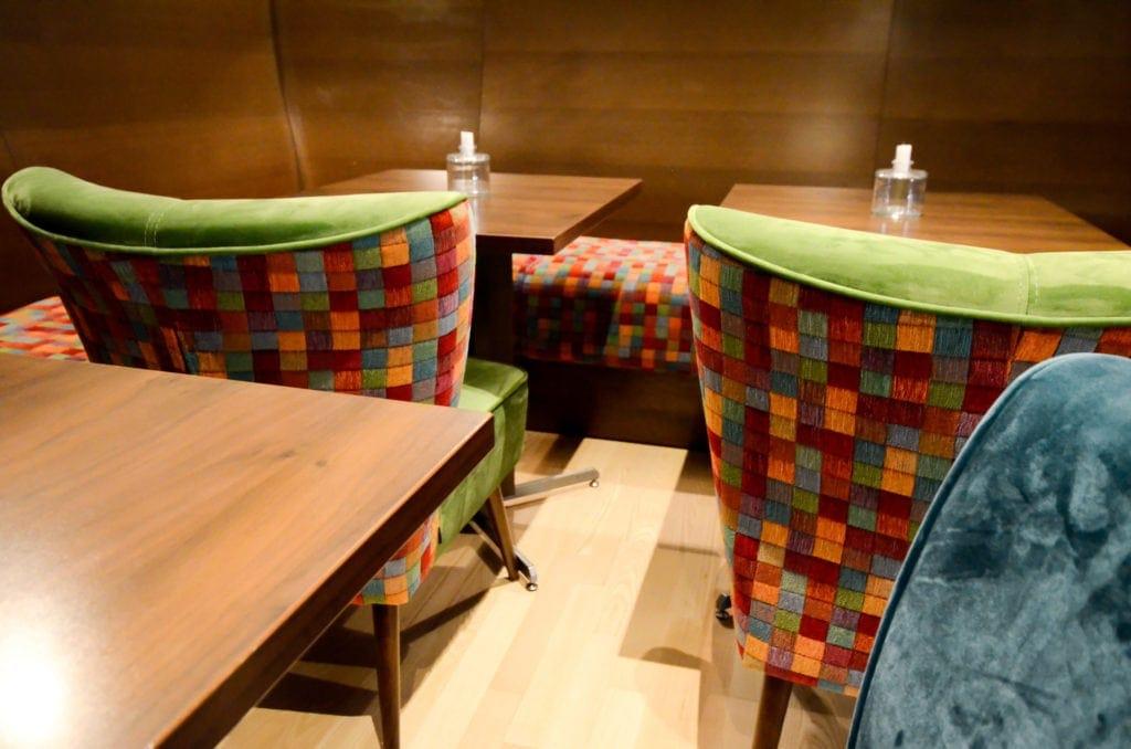 Sitzbank aus gemütlichen Polster mit Restauranttischen